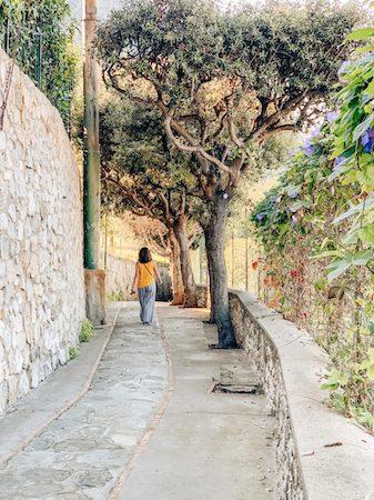 woman walking down a narrow stone road in Capri, Italy