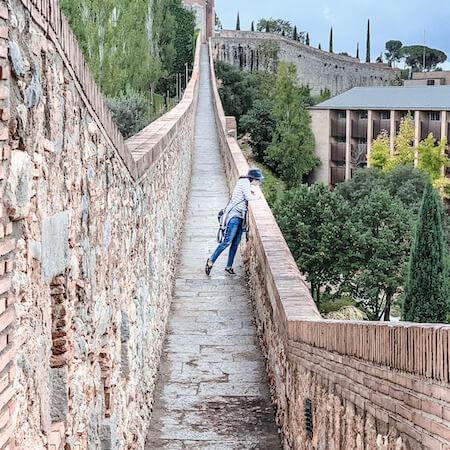 Kathy on the narrow stone city wall of Girona, Spain