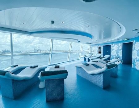 Heated loungers pointed towards large windows on a spa cruise ship