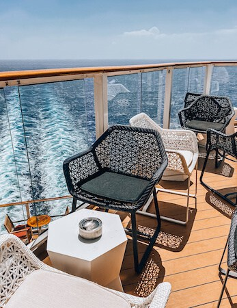 Outdoor bar seating on the back deck of cruise ship