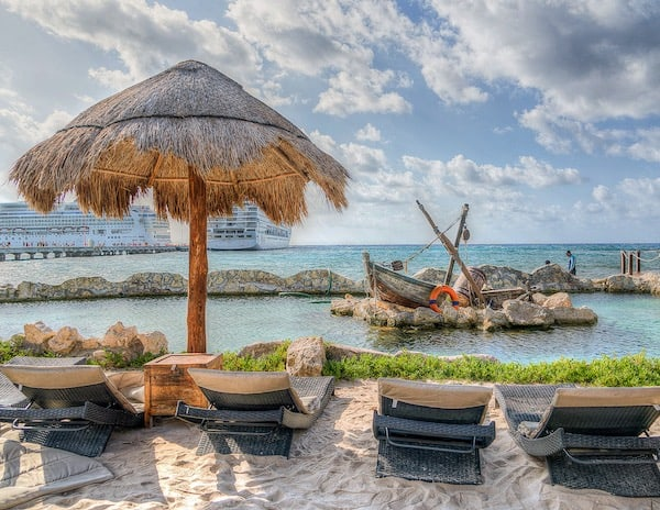 Beach chairs, strawb beach umbrella overlooking the bay and cruise ship | How to Prepare for a Cruise