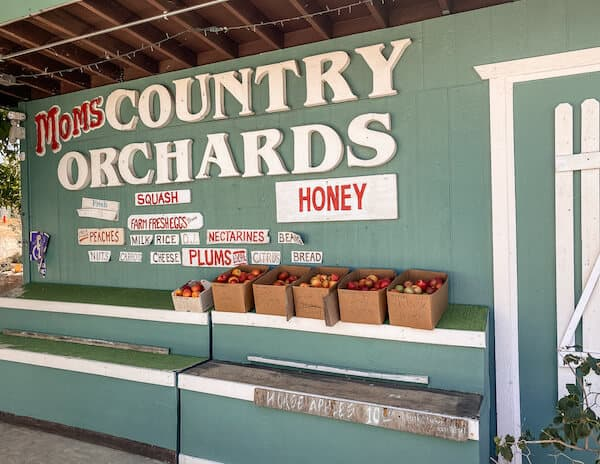 outside moms country orchards market sign with baskets of apples