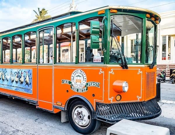 trolley, open-air windows, green top exterior, and bottom orange exterior
