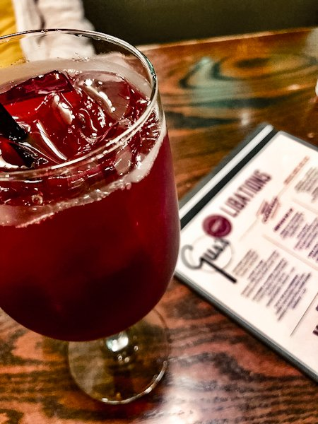 A wine glass filled with sangria and a menu